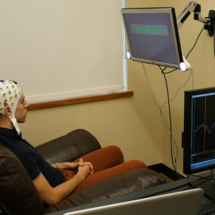 Participant wearing an electroencephalography (EEG) cap that records brain activity and sends a response to a second participant over the Internet. (University of Washington)